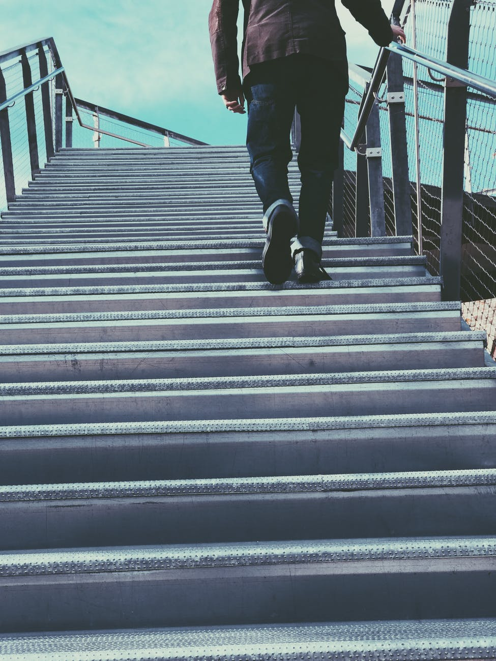 man walking on gray stairs